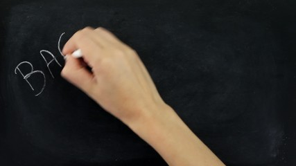 1Hand writing back to school on a blackboard
