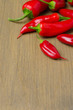 red hot chili peppers on wooden background (with space for text)