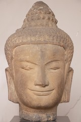 head of smiling buddha statue made by stone