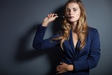 Elegant woman with e-cigarette wearing suit