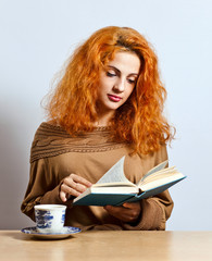 woman with book and tea cup