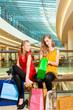 Two women friends shopping in a mall