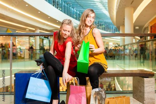 Two women friends shopping in a mall