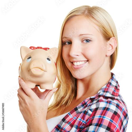 Lächelnde Frau hält ein Sparschwein