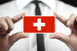 Businessman holding a business card with a Switzerland Flag