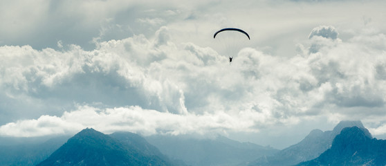 Paraglider over mountains and cloudy sky background