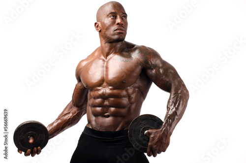 Black bodybuilder posing with round discs