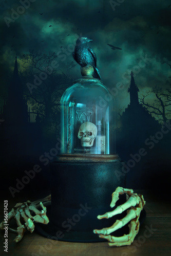 Glass bell jar with crow and skeleton hands