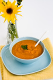 Pumpkin soup in a blue plate and a bouquet of yellow flowers