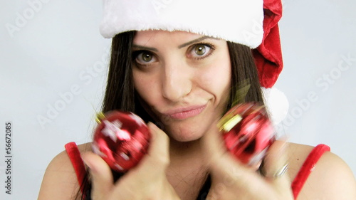 Gorgeous woman santa claus playing with christmas balls