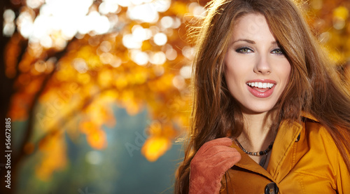 Young woman with autumn leaves in hand and fall yellow maple gar