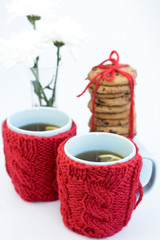 Two blue cups in knitted covers and chocolate cookies