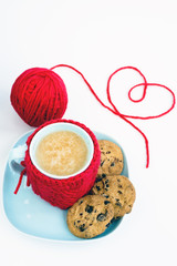 Blue cup with red knitted cover and the heart of the thread