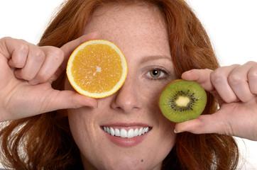 Hübsche rothaarige Frau mit Obstscheiben lächelt