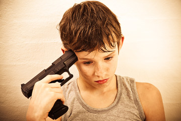 Depressed boy holding a handgun to his temple to commit suicide