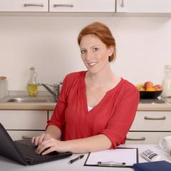Hübsche rothaarige Frau arbeitet in ihrem Homeoffice