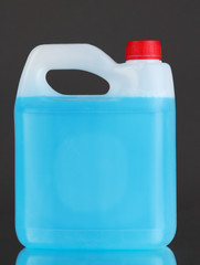 Blue liquid for car in canister on grey background