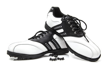 Golf shoes with spare spikes isolated on white
