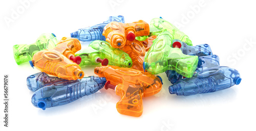 Pile of colorful plastic water pistols on a white background