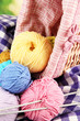 Multicolored clews in wicker basket with needles and plaid