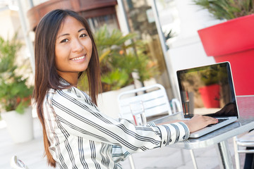 Cheerful asian girl using a laptop