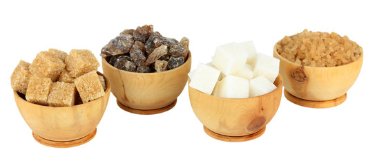 Different types of sugar in bowls isolated on white