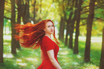 Beautiful woman with red fluttering hair