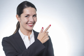 Beautiful friendly woman pointing to copy-space