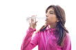 Young woman drinking water from a bottle wearing a pink jacket