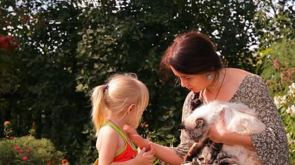 мать с двумя детьми и кошкой разговаривают, смеются