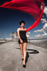 Sexy girl in black dress with red veil walking on bridge