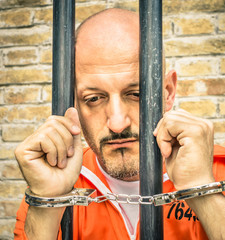 Dead Man Walking - Sad Prisoner with Handcuffs behind Bars