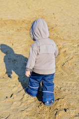 Young boy walking on the beach
