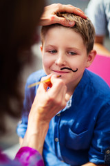Cute boy with painted mustache