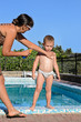 Mother applying suntan lotion to her son