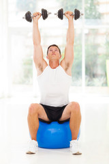 healthy man lifting up a dumbbells
