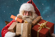 Photo of happy Santa Claus outdoors in snowfall carrying gifts t