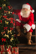 Santa Claus standing near Christmas tree in dark room