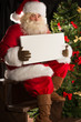Santa Claus sitting indoors at dark room near Christmas tree and