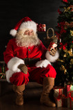Santa placing gifts under Christmas tree in dark room