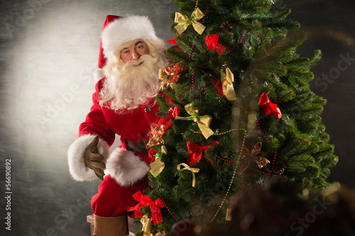 Santa Claus standing near Christmas tree