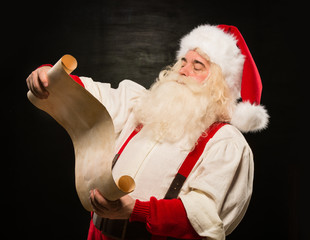 Portrait of happy Santa Claus reading Christmas letter