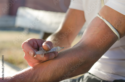 Hands of a man injecting a drug dose intravenously