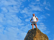 Determined man standing on mountain top