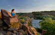 Woman meditating on a rock above a river