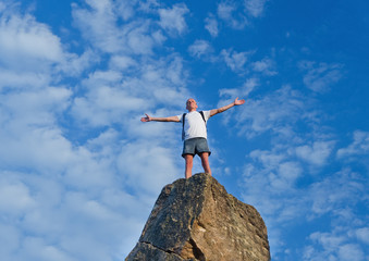 Man celebrating reaching the top of a mountain