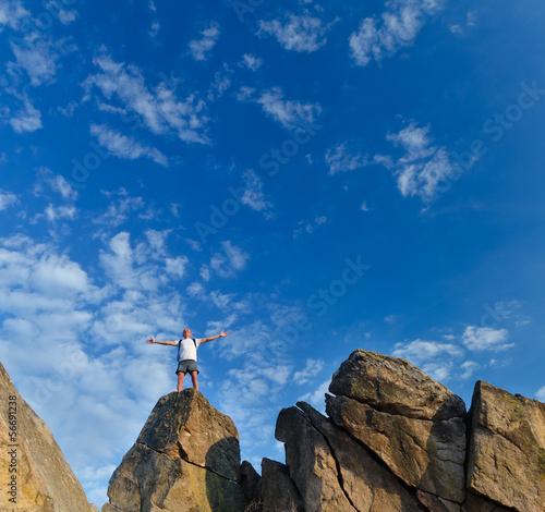 Man reaching top of a mountain