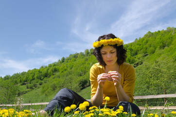 A young woman making a garland of flowers