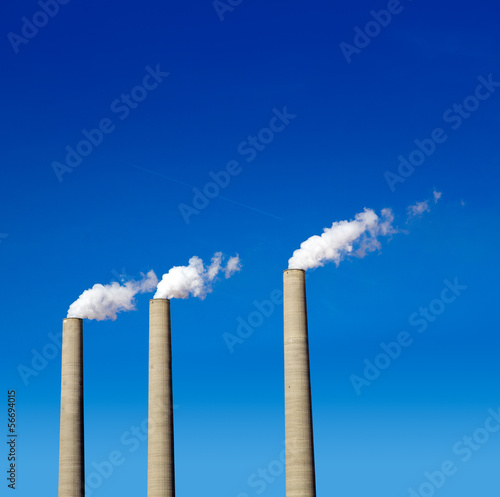 Chimney white smoke three in a row on a blue sky