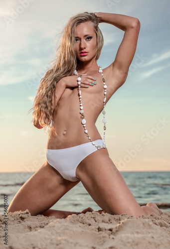 Sexy young woman with long hair topless posing on the beach